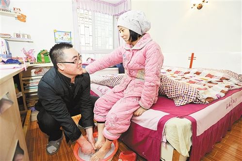 吴廷河给患病的妻子洗脚。