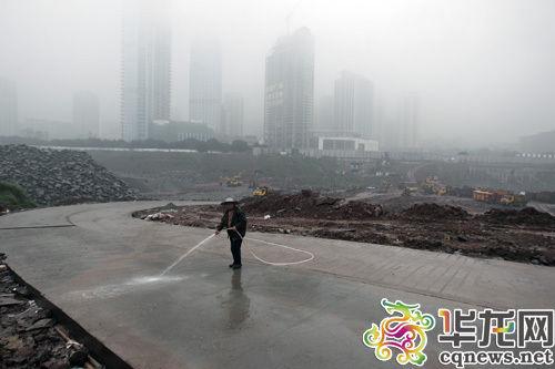 渝北区中渝国际都会土石方工地道路泥泞,工人在加紧冲洗。