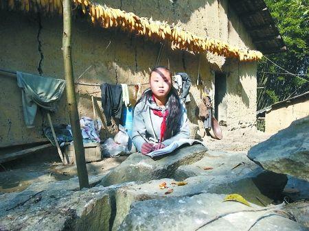 万州区孙家乡快乐村,蒲赢红正在房前的石头上做作业。