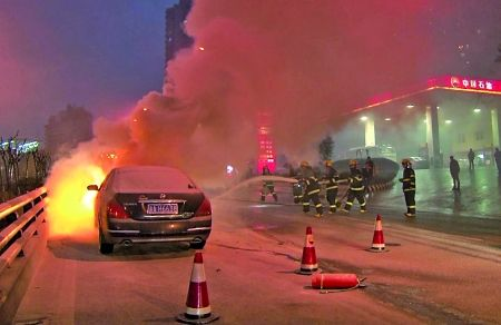 轿车自燃,消防队员在灭火。
