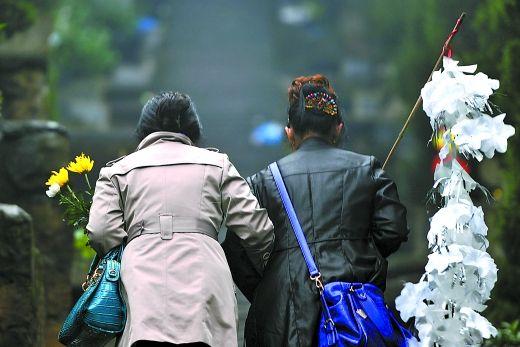 5日,南岸涂山公墓,市民拿着鲜花祭拜亲人。