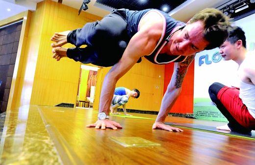 """来自美国的瑜伽教练本杰明展示""""双臂平衡""""技艺。"""
