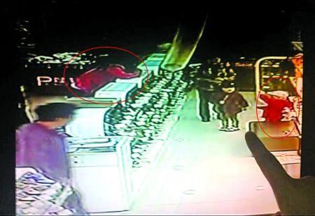 红衣女子(左)正喊儿子(红衣男孩)去拿别人遗忘在条凳上的手机 视频截图