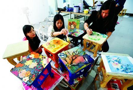 重庆工商大学,同学们正在制作的凳子上作画。