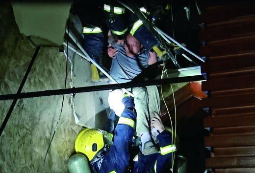消防队员将昏迷的工人从吊顶层里救出。