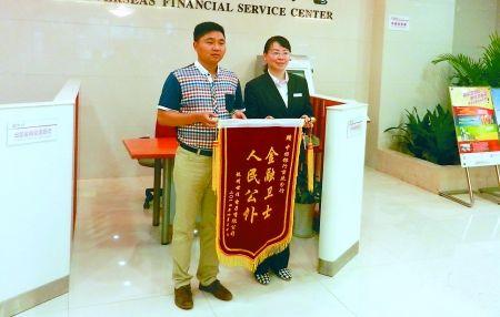 张先生(左)给中国银行重庆市分行赠送锦旗表示感谢