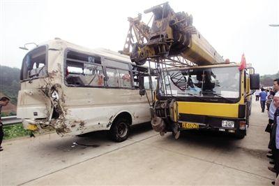 10日,巴南区天星寺镇车祸现场,出事中巴被吊车从山坡下拉上公路。