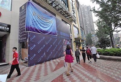 """昨日,观音桥北城旺角广场的""""未知数""""酒吧临街面,已盖上广告布。"""