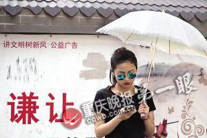 美女顶着烈日打着伞过红绿灯时还在耍手机。