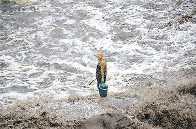 钓鱼老人江边遇涨水被困 吊车出动将他钓上岸