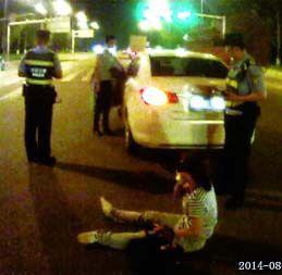 闪着应急灯的白色轿车停在十字路口中央,几米外一个浑身擦伤女子坐在地上。