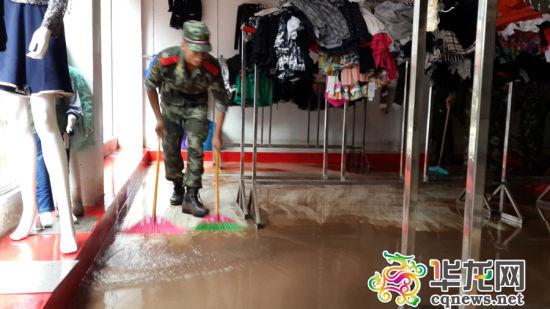 武警战士在帮助商家清理店铺的积水。