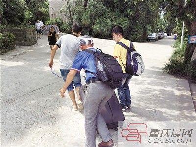走上坡时,父亲为儿子推行李箱。