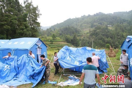 图为民兵应急分队正在为灾民搭建帐篷。