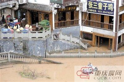磁器口古镇,一市民在洪水中划着皮艇。