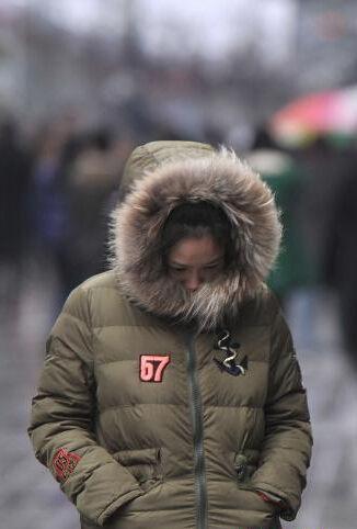 图为一市民戴着帽子露出一半脸行走在步行街上。