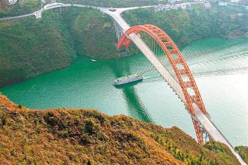 十一月二十五日,一艘满载着游客的客轮在三峡巫峡红叶的掩映下向下游驶去。