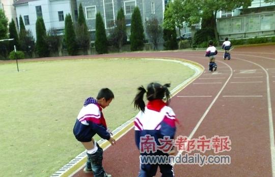 3名男生脱下裤子围着操场跑步的同时,有女学生在旁边监督