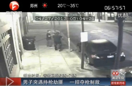 监控拍下男子突遭持枪劫匪指头冷静夺枪